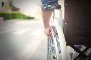 A close up of a man as he rolls the wheel of his wheelchair.